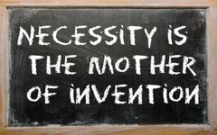 "Proverb ""necessity is the mother of invention"" written on a blackboard Stock Photos"
