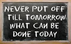 "proverb ""never put off till tomorrow what can be done today"" written on a bla - stock photo"