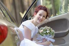 A bride holding a bouquet while sitting in a car Stock Photos