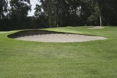 A sand trap in front of a green on a golf course Stock Photos