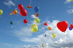 Colored helium balloons with messages floating in the sky above Stock Photos