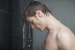 Man standing in shower and looking down - stock photo