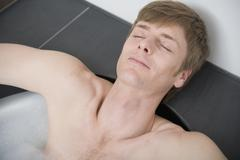 Man lying in bathtub with eyes closed Stock Photos