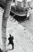 Man walking along riverbank near docked motorboat Stock Photos