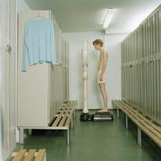 A young man standing on a scale in a locker room Stock Photos