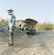 A motorcycle racer standing next to a burned-out car Stock Photos