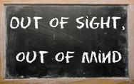 "Stock Illustration of proverb ""out of sight, out of mind"" written on a blackboard"