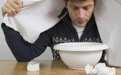 Stock Photo of A man with a cold breathing steam from a bowl