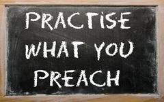 "Stock Photo of proverb ""practise what you preach"" written on a blackboard"