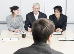 Three people interviewing a candidate in an office Stock Photos