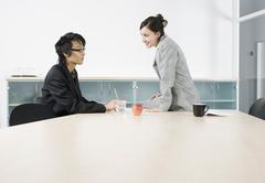 A man and a woman having a discussion in a conference room Stock Photos