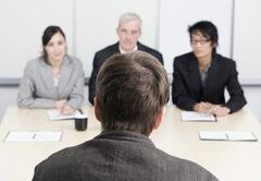 A man being interviewed by three people Stock Photos