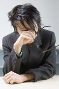 An Asian businessman experiencing stress and exhaustion Stock Photos