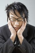 An Asian businessman resting his head in his hands Stock Photos
