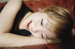 Stock Photo of A Japanese woman lying on her side, smiling