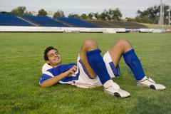 A soccer player resting on a soccer ball Stock Photos