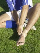 A soccer player taping up his ankle - stock photo