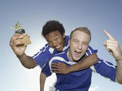 Two soccer players celebrating with a trophy Stock Photos