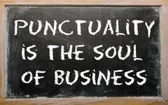 "proverb ""punctuality is the soul of business"" written on a blackboard - stock photo"