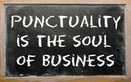 "Stock Photo of proverb ""punctuality is the soul of business"" written on a blackboard"