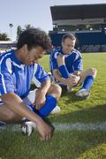 Two soccer players sitting on a soccer field, laughing Stock Photos