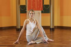 Young woman stretching on floor Stock Photos