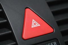 Push button on car dashboard for hazard lights Stock Photos