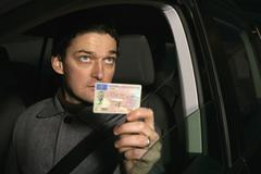 Man sitting in car and holding his ID card - stock photo