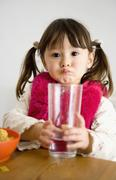 Stock Photo of Young girl with pigtails sitting at table and holding glass of water
