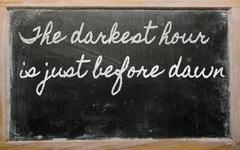 Stock Illustration of expression -  the darkest hour is just before dawn - written on a school blac