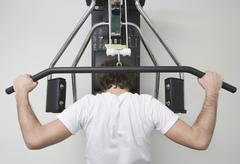 Young man weight training in a gym Stock Photos