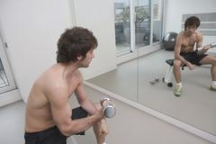 Stock Photo of Young man sitting in gym using hand weight