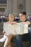 Young Chinese couple sitting on steps and holding map, New York City Stock Photos