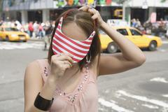 Young woman putting on sun visor - stock photo