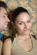 Man leaning over to whisper into woman's ear - stock photo