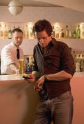 Young man waiting at bar with bartender in the background Stock Photos