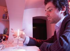 Young man sits alone drinking a cocktail in a bar - stock photo