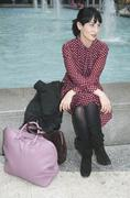 Young woman sitting down near a fountain with luggage, New York City Stock Photos