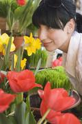 Young woman smelling a daffodil in a florist Stock Photos