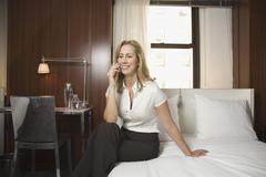 Nainen käyttää matkapuhelin istuen sängyllä hotellihuoneessa Kuvituskuvat