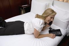 Nainen makaa sängyssä hotellihuoneessa käyttäen puhelin Kuvituskuvat