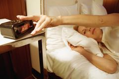 Woman lying in bed with hand on alarm clock Stock Photos