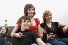 Three young adults sitting on sofa drinking beer and watching television Stock Photos