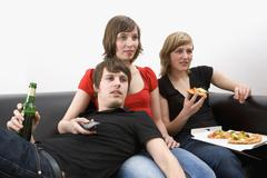 Three young adults sitting on sofa eating pizza, drinking beer, and watching Stock Photos