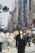 Stock Photo of Businesswoman standing near pedestrian crossing on busy street wearing pollution