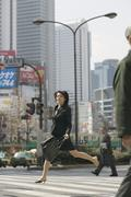 Businesswoman mid-air whilst crossing street, Tokyo, Japan Stock Photos