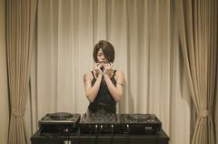 Stock Photo of Young woman standing behind turntables