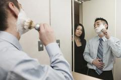Businessman applying shaving cream to face whilst woman stands behind watching - stock photo