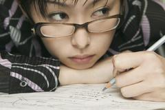 Young woman leaning on desk studying - stock photo