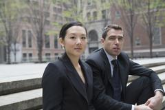 Businessman and businesswoman sitting on steps Stock Photos